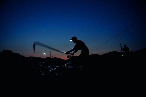 """戴上矿灯,背着篓筐,在夜里就开始""""淘金""""的拾荒人。 图/视觉中国"""